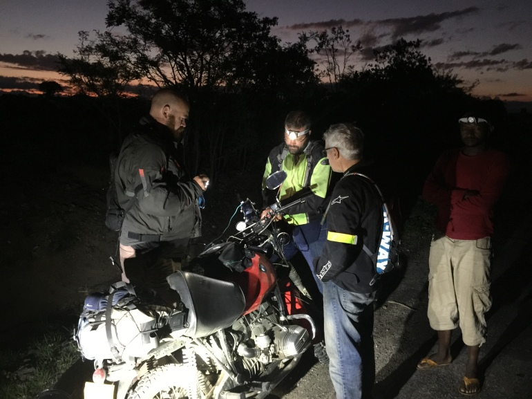 Philip fixes his broken throttle cable roadside, early morning in Tanzania