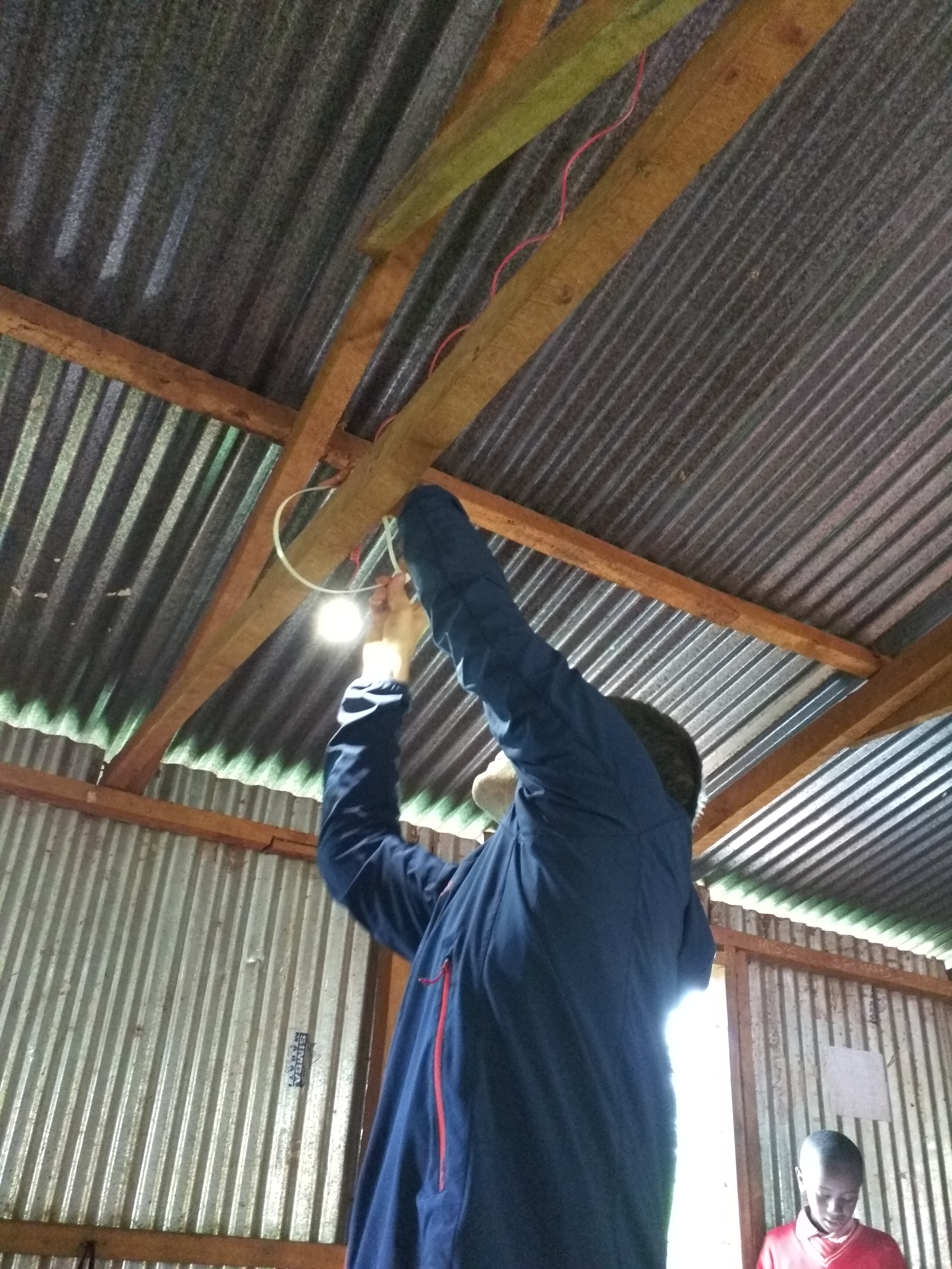 Jeff Crystal of Voltaic Systems installs lights in one of the classrooms.